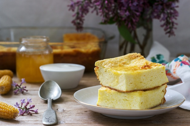 Traditional romanian or moldavian cottage cheese casserole with cornmeal, served with honey and sour cream.