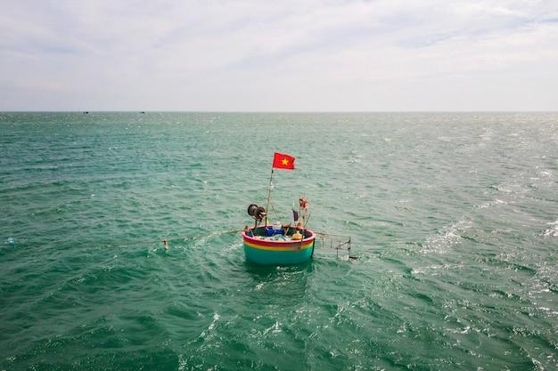 Traditional, round boats on sea, with vietnamese flag, mui ne vietnam,