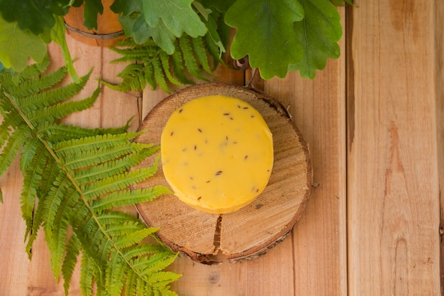 Traditional round cheese with caraway seeds on a wooden plate with leaves around