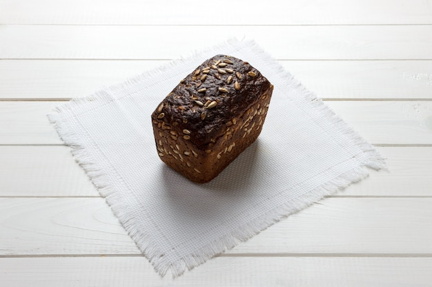 Traditional round rye bread on white fabrick cloth. bread on wooden background