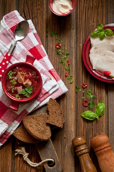 Traditional russian beet soup borsch with bacon, sour cream and chopped parsley