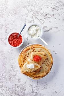 伝統的なロシアのクレープブリニは、赤キャビア、新鮮なサワークリームが入ったプレートに積み重ねられています。マースレニツァの伝統的なロシアのお祭りの食事。ロシア料理、ロシアのキッチン。上面図。