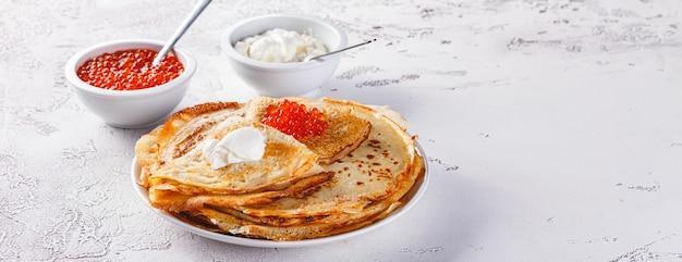伝統的なロシアのクレープブリニは、赤キャビア、新鮮なサワークリームが入ったプレートに積み重ねられています。マースレニツァの伝統的なロシアのお祭りの食事。ロシア料理、ロシアのキッチン