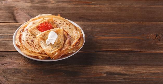 伝統的なロシアのクレープブリニは、赤キャビア、新鮮なサワークリーモンのダークウッドのテーブルが付いたプレートに積み重ねられています。マースレニツァの伝統的なロシアのお祭りの食事。長く広いバナー。テキスト用のスペース
