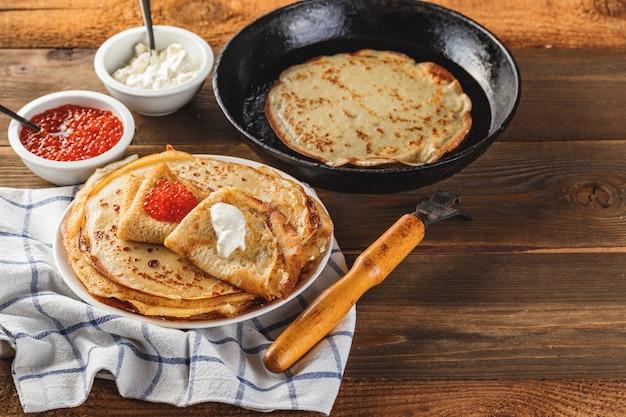 伝統的なロシアのクレープブリニは、赤キャビア、新鮮なサワークリームオンダークウッドのテーブルとプレートに積み重ねられました。マースレニツァの伝統的なロシアのお祭りの食事。ロシア料理、ロシアのキッチン