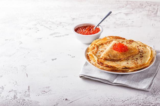 伝統的なロシアのクレープブリニは、赤キャビアのプレートに積み重ねられています。マースレニツァの伝統的なロシアのお祭りの食事。ロシア料理、ロシアのキッチン