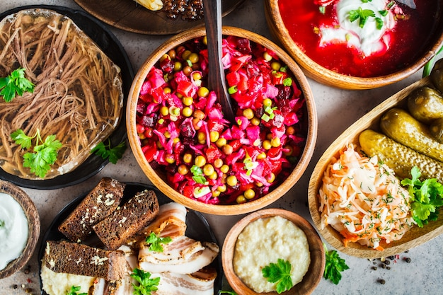 Traditional russian cuisine concept. borsch, jellied meat, lard, crepes, salad vinaigrette and sauerkraut, top view, gray background.