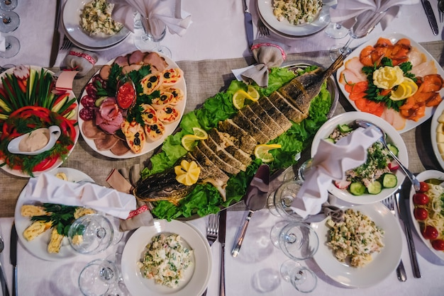 Traditional russian cuisine with baked stuffed pike and other snacks on the festive table in the restaurant