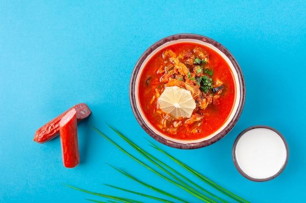 Традиционное русское блюдо солянка, красный суп с разным мясом, колбаса, зелень, сметана на синем столе, крупный план, вид сверху, место для текста, пространство для копирования, горизонтальный