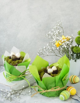 Traditional russian easter cottage cheese dessert, orthodox paskha on grey concrete  table with kulich cakes, flowers, colored eggs.