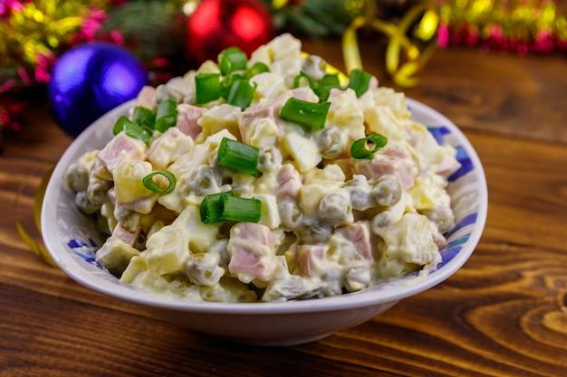 Традиционный русский праздничный салат оливье и новогодние украшения на деревянном столе