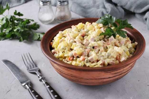 Traditional russian festive salad olivier in bowl against grey surface, closeup, horizontal format