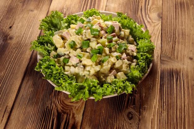 Традиционный русский праздничный салат оливье на деревянном столе
