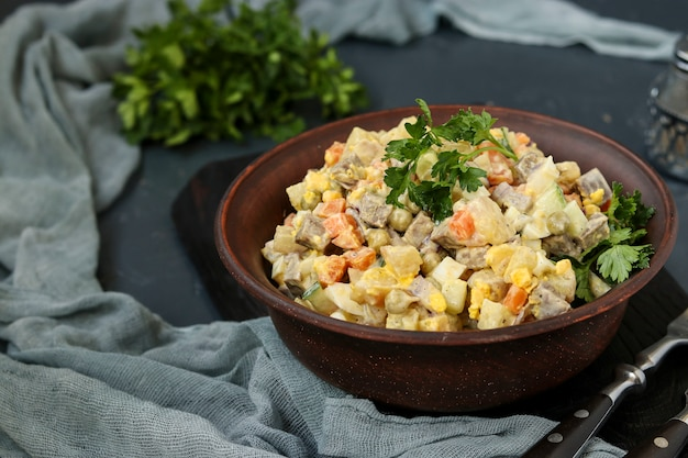 Traditional russian festive salad olivier with tongue in a bowl against a dark surface, horizontal orientation