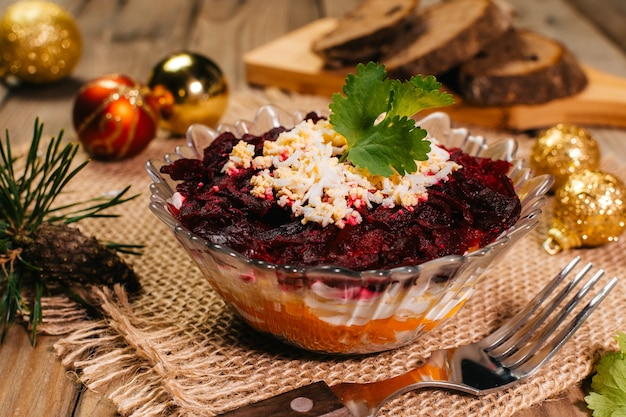 Traditional russian herring under a fur coat in transparent plate with parsley