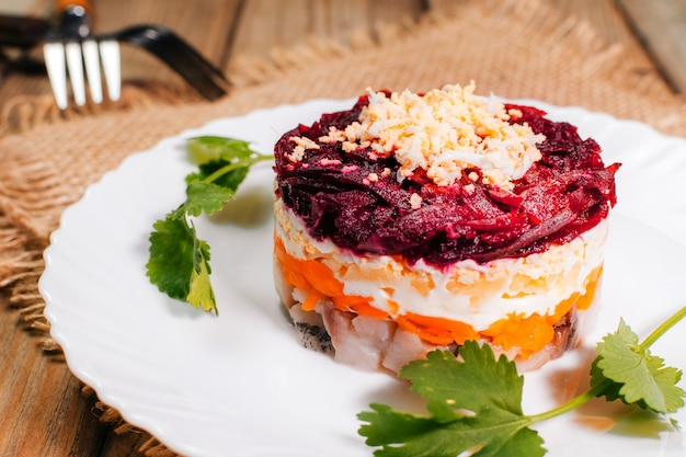Традиционная русская сельдь под шубой на белой тарелке с петрушкой. деревенский стиль