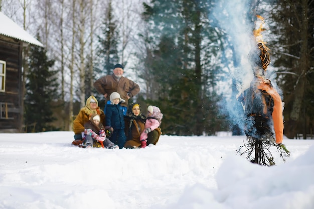 Traditional russian holiday in early spring. seeing off winter. mardi gras. family with children in the winter in the park.