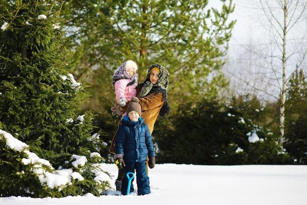 Традиционный русский праздник ранней весной. проводы зимы. вторник на масляной неделе. семья с детьми зимой в парке.