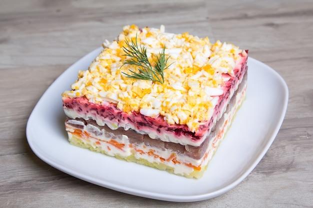 Традиционный русский многослойный салат из сельди, свеклы, картофеля, моркови и яиц.