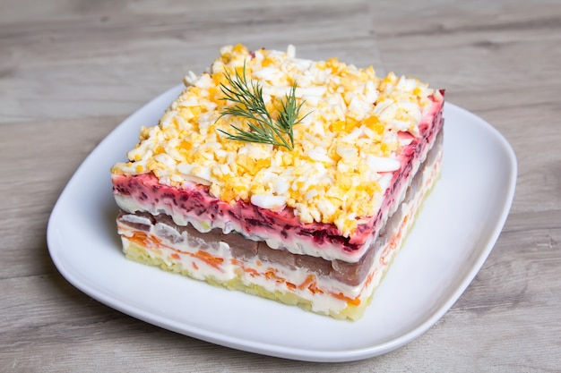 Traditional russian multilayered salad from herring, beets, potatoes, carrots and eggs.