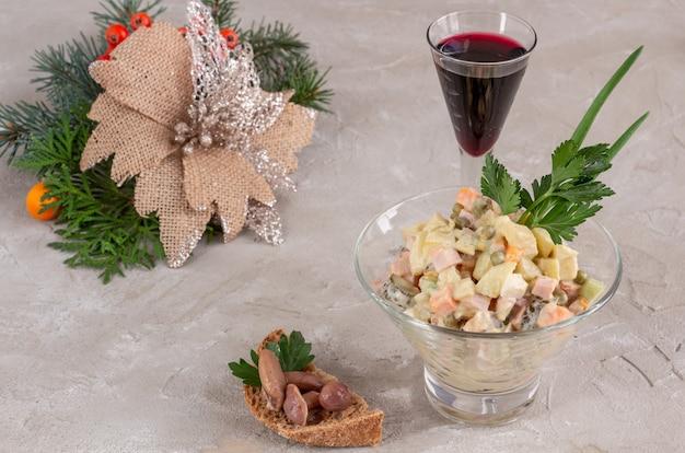 Традиционный русский новогодний салат оливье и бокал вина на бетонном фоне