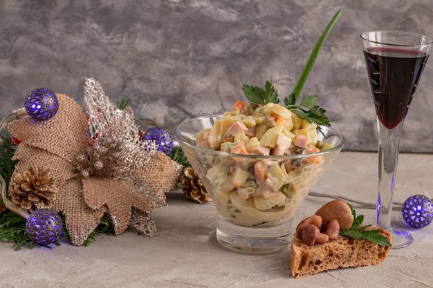 Традиционный русский новогодний салат оливье и бокал вина с новогодним или рождественским салатом