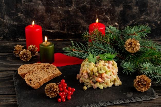 Традиционный русский новогодний салат olivier new years или рождественский салат, служащий на черном фоне