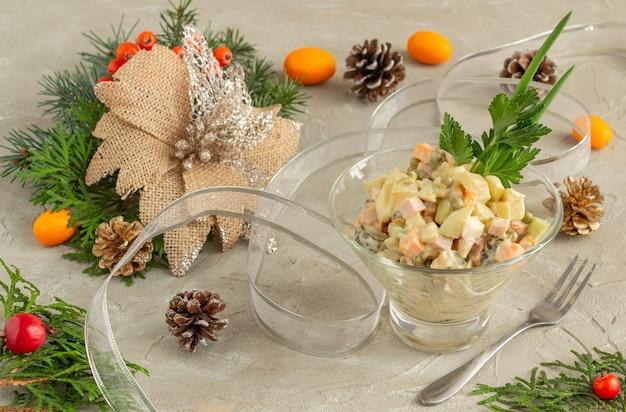 Традиционный русский новогодний салат оливье, подающий рождественский салат на бетонном фоне