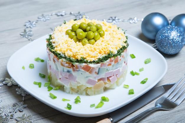 Традиционный русский салат оливье на белой тарелке