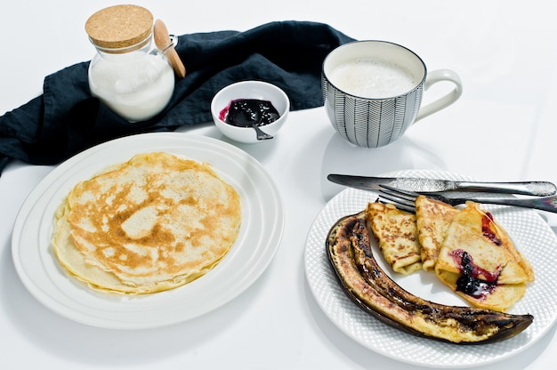 Traditional russian pancakes with blueberry jam, breakfast with coffee.