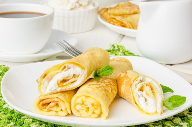 Traditional russian pancakes with sweet cottage cheese, raisins and cherry sauce for breakfast
