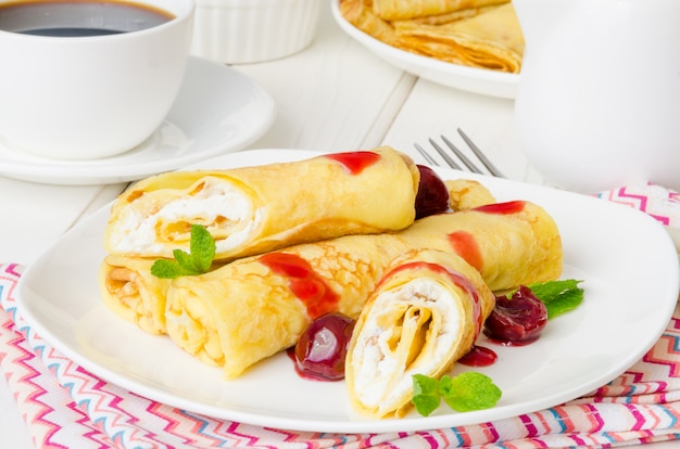 Traditional russian pancakes with sweet cottage cheese, raisins and cherry sauce