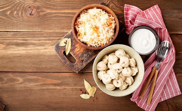 사워 크림과 나무 배경 위에 사워 크림과 함께 소금에 절인 양배추와 전통적인 러시아 pelmeni 만두. 평면도, 평면 누워. 텍스트를 놓습니다.