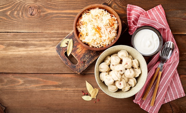 Traditional russian pelmeni dumplings with sour cream and sauerkraut with sour cream over wooden background. top view, flat lay. place for text.