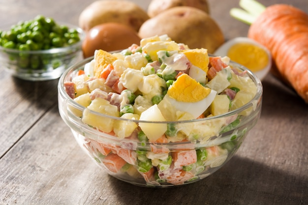 Traditional russian salad in bowl. olivier salad on wooden table.