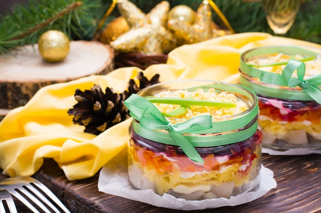 Traditional russian salad, herring under a fur coat in bowls in new year's decorations