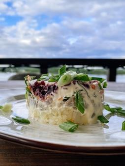 Традиционный русский салат из сельди под шубой на природе