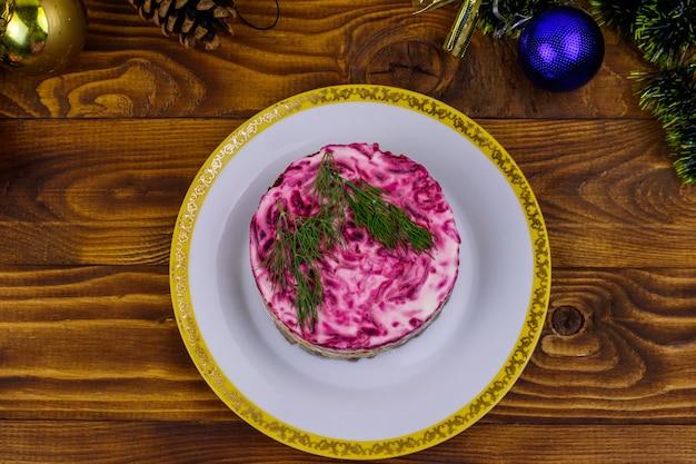 Традиционный русский салат «селедка под шубой» (шуба) и елочные игрушки на деревянном столе. вид сверху