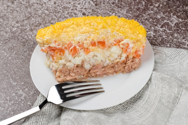 Traditional russian salad mimosa with vegetables and fish. layered salad with potatoes, tuna, carrot, onion, eggs and mayonnaise.