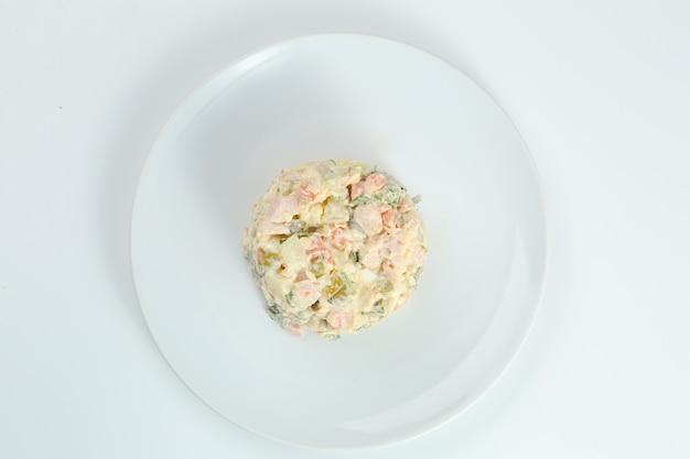 삶은 야채와 고기를 그릇에 담은 전통 러시아 샐러드 올리비에. 러시아 새 해 또는 크리스마스 흰색 절연입니다.