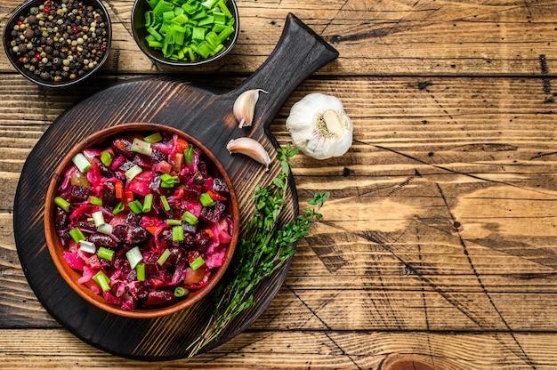 Традиционный русский салат-винегрет с отварными овощами, маринованными огурцами в миске. деревянный фон. вид сверху. скопируйте пространство.