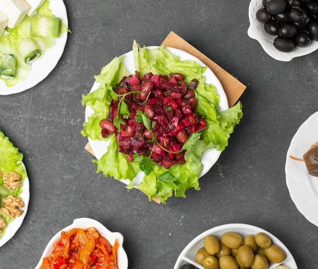 Традиционный русский салат винегрет с листьями салата. вид сверху.