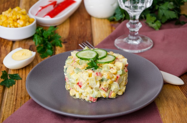 Traditional russian salad with crab sticks, fresh cucumbers, corn and boiled eggs