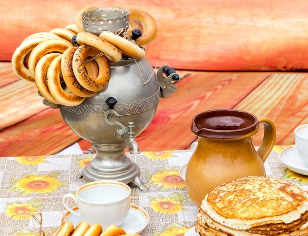 Традиционный русский самовар с вкусными бубликами и керамической посудой
