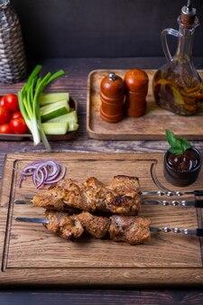 Традиционный русский шашлык на шпажках с овощами. свинина на гриле (шашлык). крупный план.