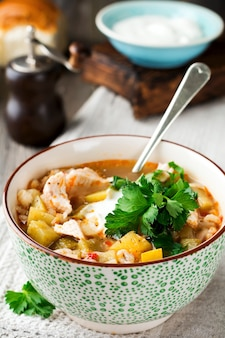 Traditional russian soup rassolnik pickled cucumber, barley, chicken, tomatoes and parsley in ceramic bowl