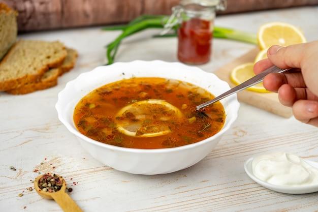 Традиционная русская суповая солянка. суп из солянки с мясом, лимоном и оливками. подается со сметаной
