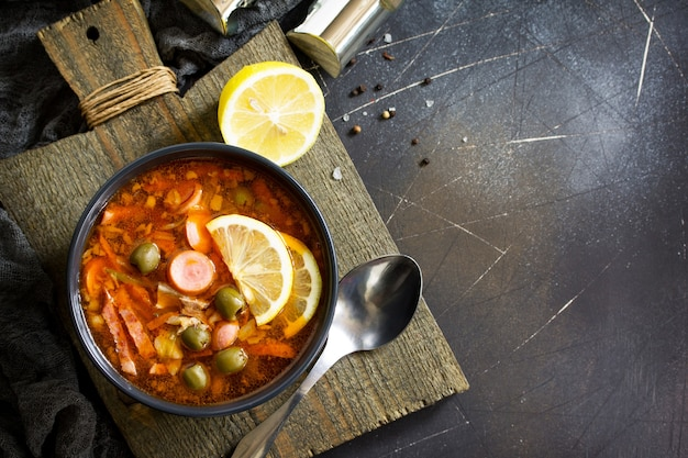 Traditional russian soup solyanka with meat sausages vegetables capers pickles and olives