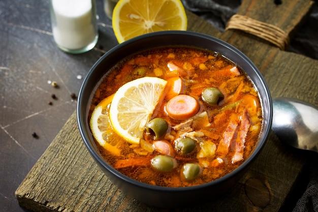 Традиционный русский суп солянка с мясными колбасами овощи каперсы деревенский стиль