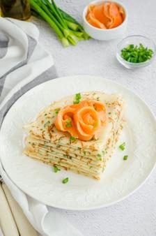 Традиционные русские тонкие блины или блины с сыром, зеленью и копченым лососем на белой тарелке на светлом фоне. праздничная масленица. вертикальная ориентация.